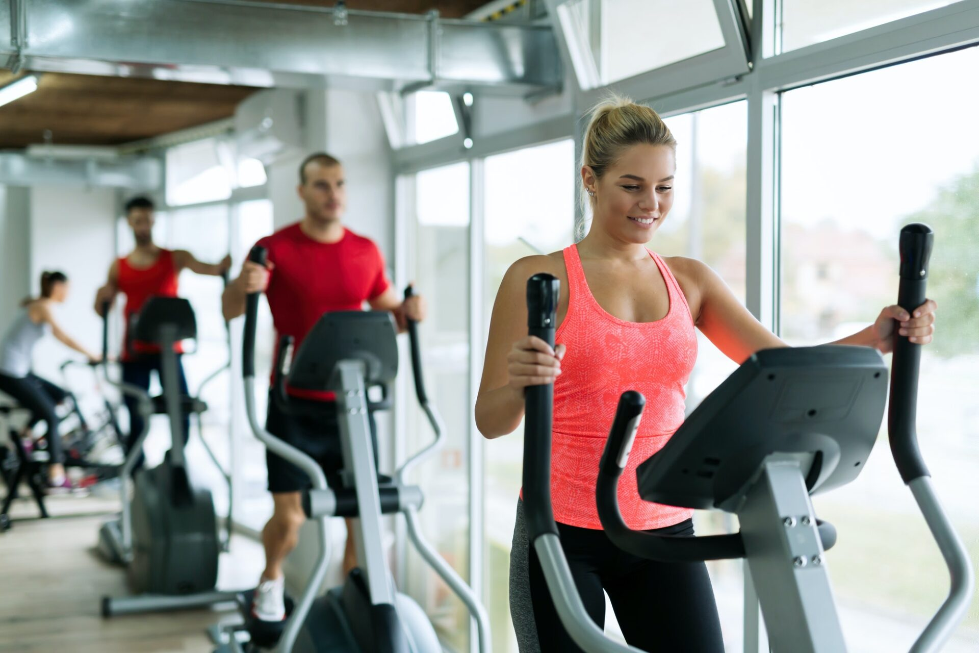 People doing on elliptical trainer in gym